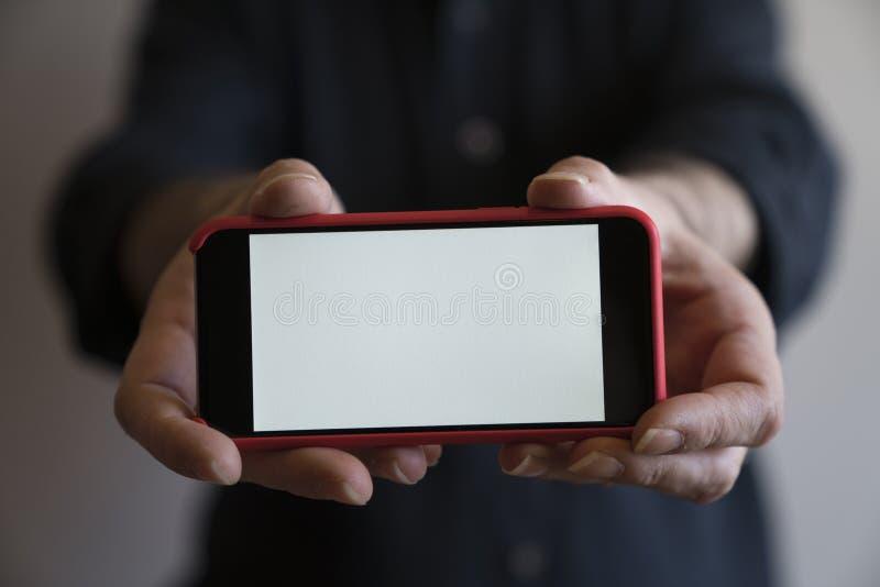 Mofa del teléfono del color rojo de las manos de la maqueta encima de la exhibición de la tenencia de la pantalla blan foto de archivo