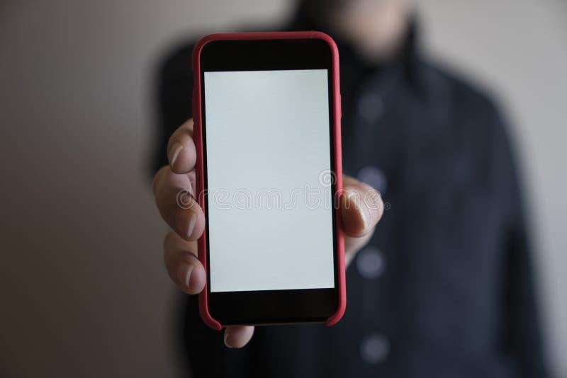 Mofa del teléfono del color rojo de las manos de la maqueta encima de la exhibición de la tenencia de la pantalla blan imágenes de archivo libres de regalías