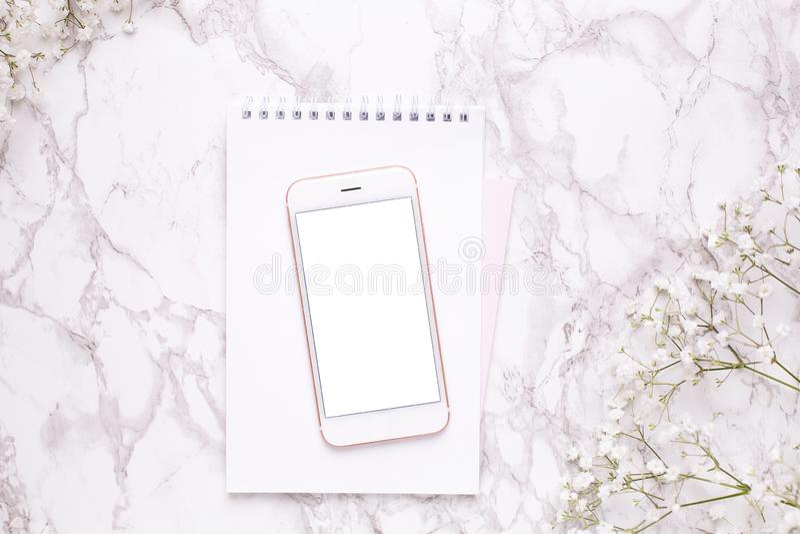 Mofa del teléfono móvil para arriba y flores blancas en la opinión de sobremesa de mármol en estilo puesto plano Escritorio d imágenes de archivo libres de regalías
