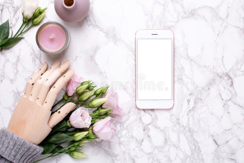 Mofa del teléfono móvil para arriba y mano de madera con las flores rosadas en el fondo de mármol fotos de archivo