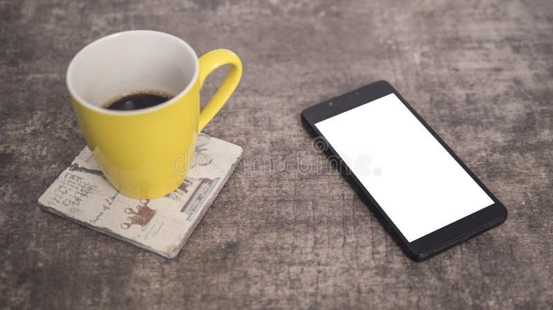 Mofa elegante del teléfono para arriba en la tabla y una taza de café amarilla imagenes de archivo
