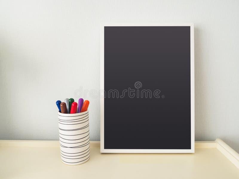 Mofa en blanco encima de la pluma colorida del capítulo de la pizarra en la tabla foto de archivo