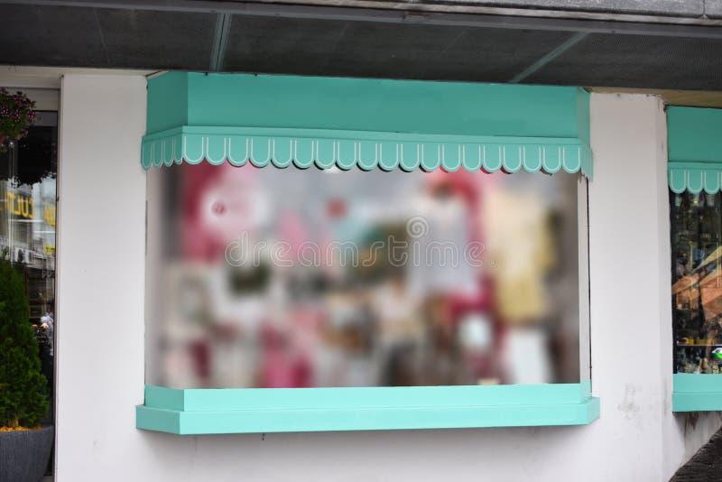 Mofa en blanco para arriba de la ventana del escaparate de la calle de la tienda foto de archivo