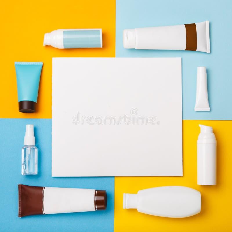 Mofa encima de los cosméticos del cuidado de piel del verano en fondo amarillo y azul foto de archivo