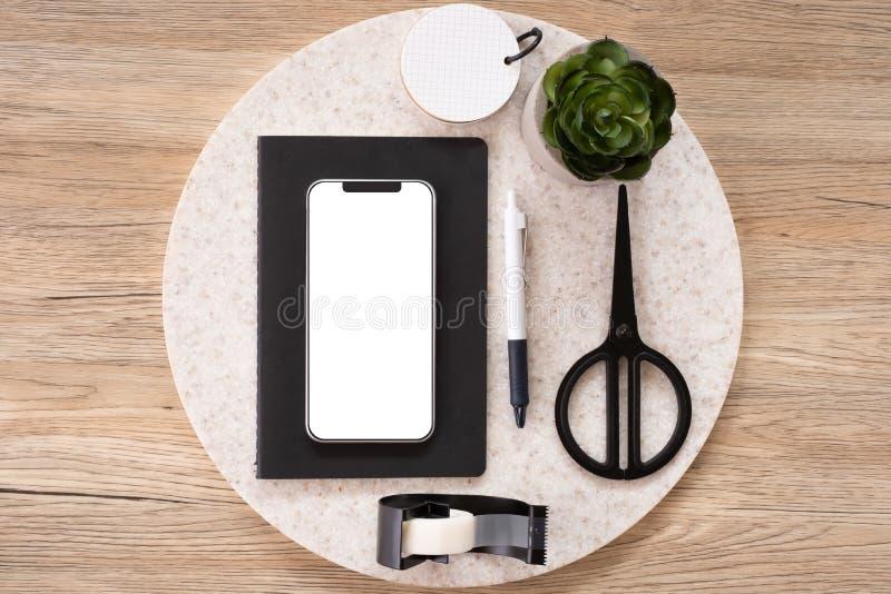 Mofa móvil para arriba en la opinión de sobremesa del escritorio de oficina con los efectos de escritorio, cuaderno, planta en fo imagen de archivo libre de regalías