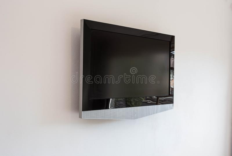 Mofa negra de la maqueta de la pantalla de la televisión del LED TV para arriba, espacio en blanco en el fondo blanco de la pared imagen de archivo libre de regalías