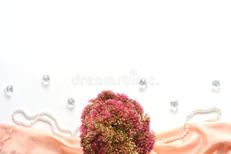 Mofa para arriba con las flores en la seda blanca foto de archivo libre de regalías