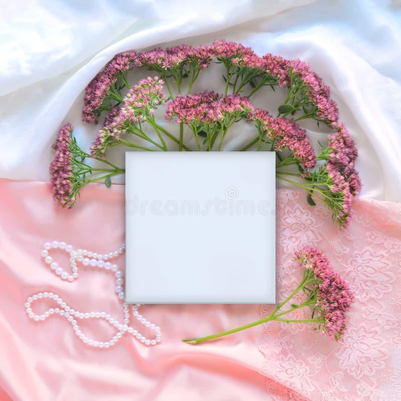 Mofa para arriba con las flores en la seda blanca imágenes de archivo libres de regalías