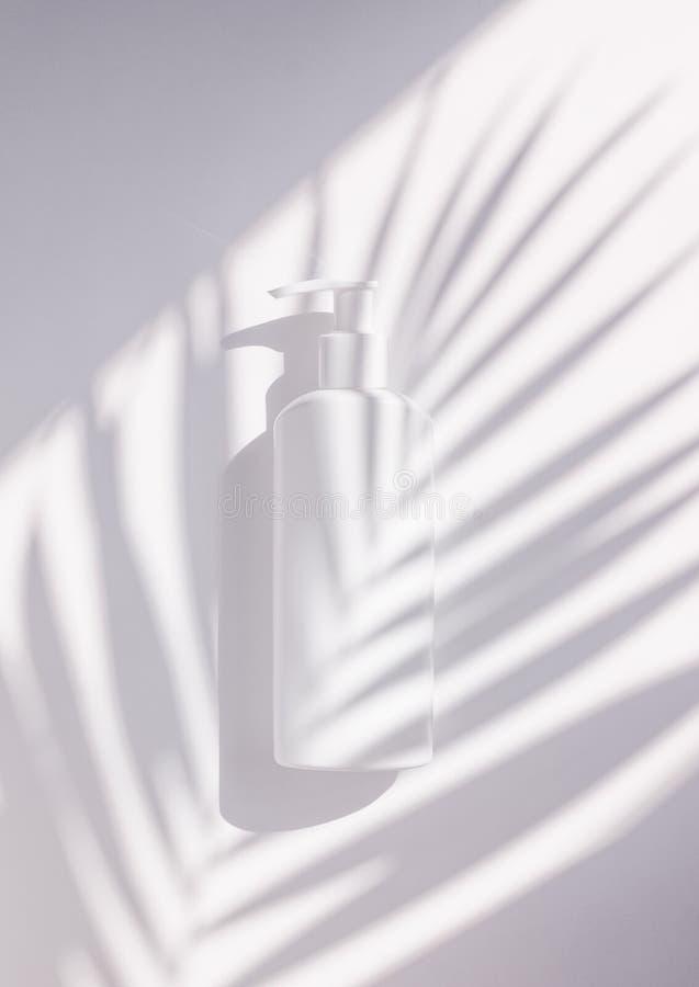 Mofa plástica de empaquetado cosmética del tiro minimalistic creativo para arriba con las hojas de palma de la sombra Maqueta par imagen de archivo