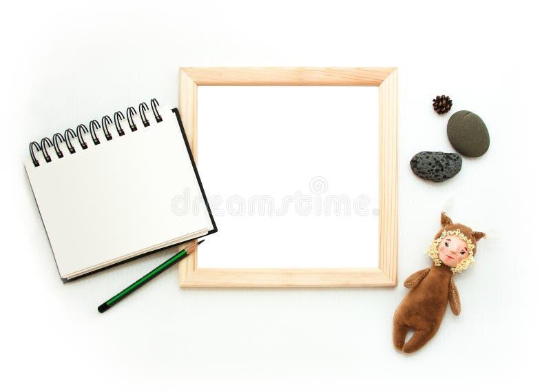 Mofa puesta plana para arriba, visión superior, marco de madera, ardilla del juguete, lápiz, cuaderno de notas, piedras Disposi fotografía de archivo libre de regalías