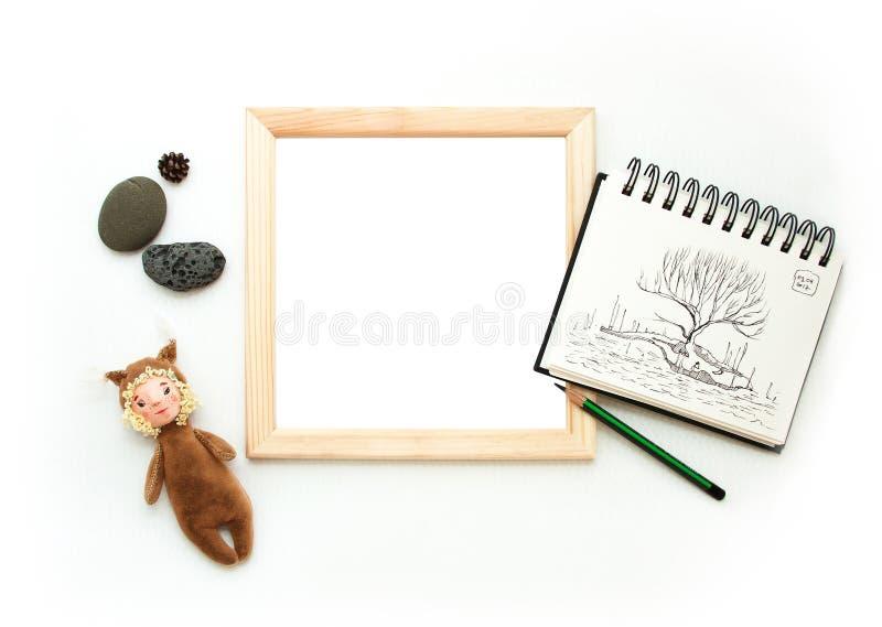Mofa puesta plana para arriba, visión superior, marco de madera, ardilla del juguete, lápiz, cuaderno de notas, piedras Disposi fotos de archivo