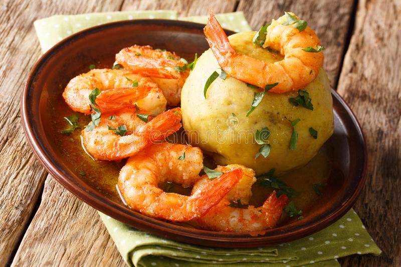 Mofongo mashed plantains, garlic and chicharron served with shrimps and broth close-up on a plate. horizontal, rustic style royalty free stock photography