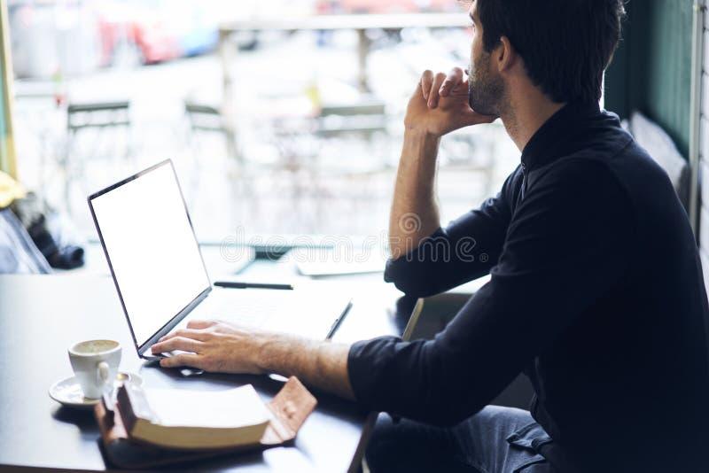 Mogen ägare av en affär i en svart skjorta genom att använda fri anslutning i coffee shop arkivfoton