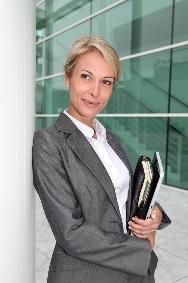 Mogen affärskvinna med dagordningbenägenhet på väggen royaltyfria foton