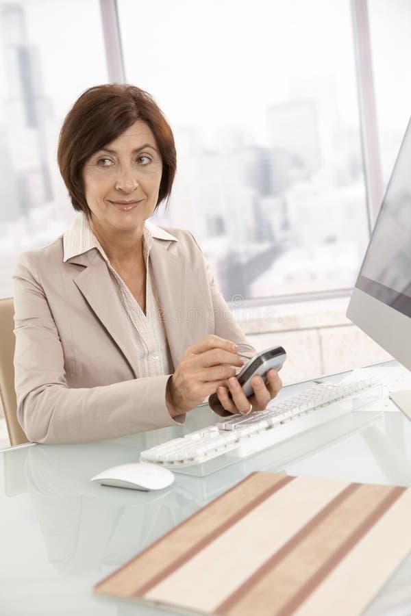 Mogen affärskvinna som använder smartphonen royaltyfri foto