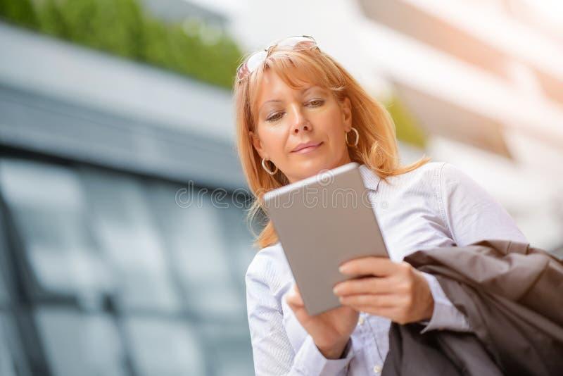 Mogen affärskvinna som arbetar på en digital minnestavla arkivbilder