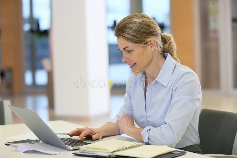 Mogen affärskvinna som arbetar på finansiellt projekt royaltyfri bild