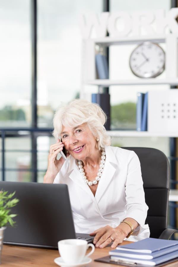 Mogen affärskvinna som i regeringsställning arbetar royaltyfri bild