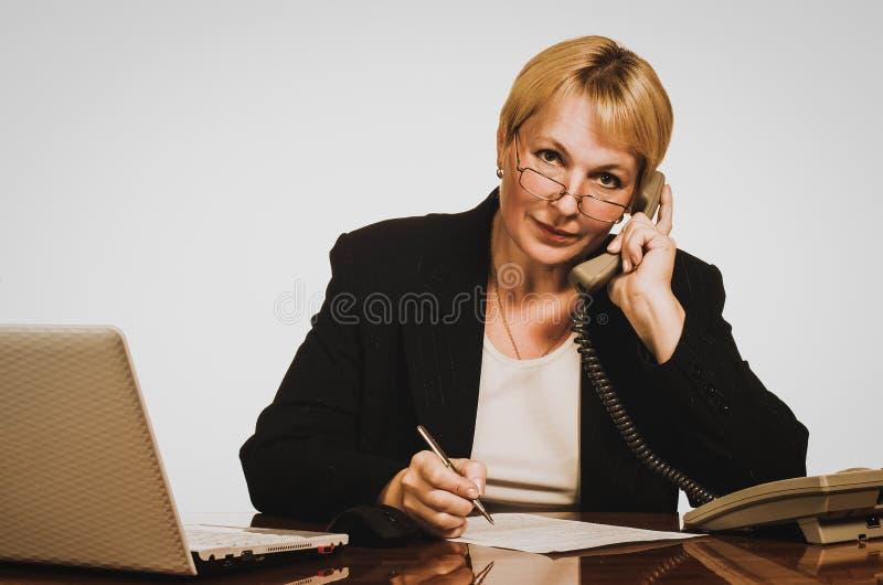 Mogen affärskvinna som kallar på telefonen på hennes arbetsplats arkivbilder