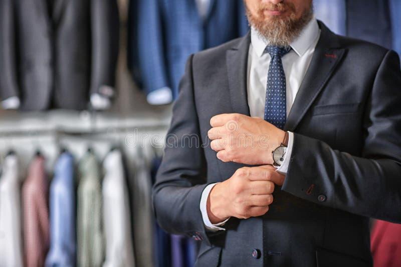 Mogen affärsman i dräkt med armbandsuret i menswearlager royaltyfria bilder