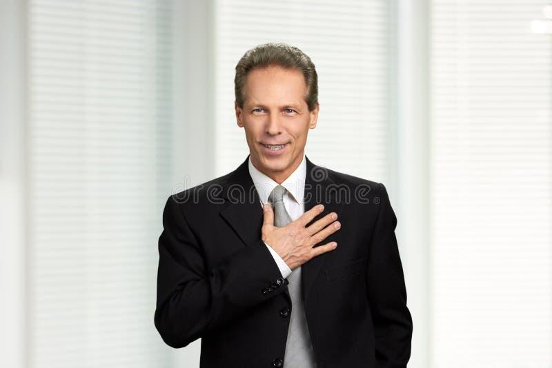 Mogen affärsman med handen på bröstkorg arkivbilder