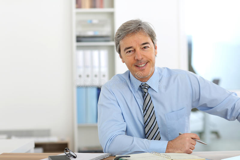 Mogen affärsman på kontoret arkivfoto
