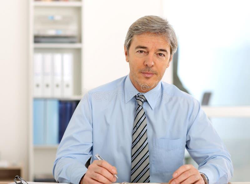 Mogen affärsman på kontorsarbete arkivbilder