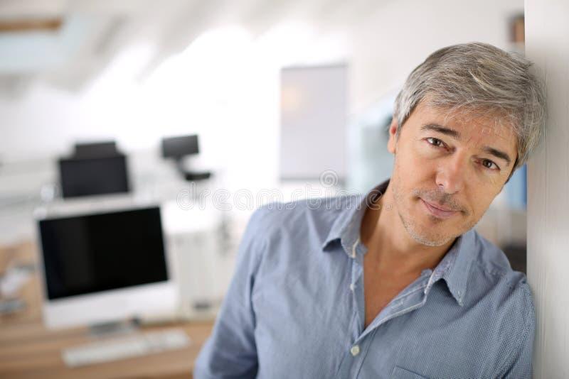 Mogen affärsman på kontorsbenägenheten på väggen royaltyfria foton