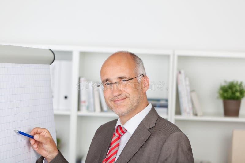 Mogen affärsman Pointing At Flipchart arkivfoton