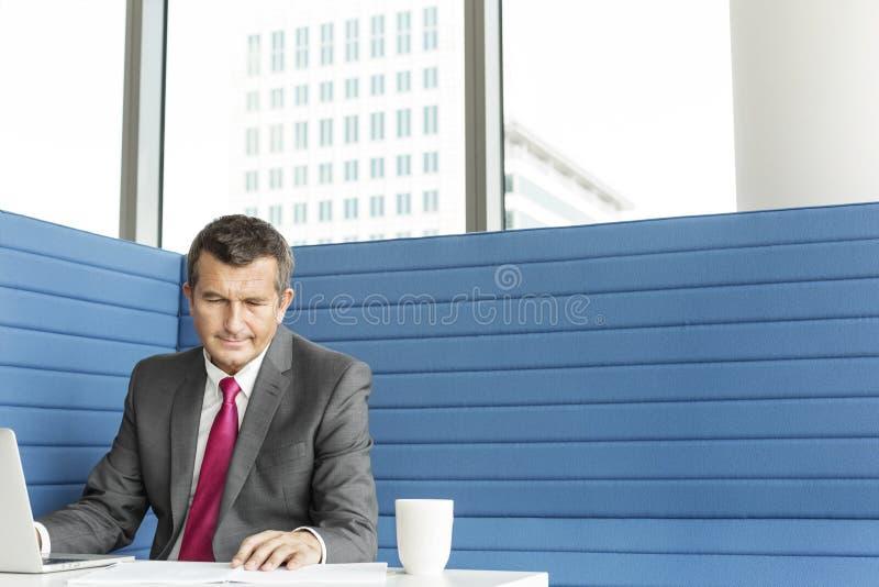 Mogen affärsman som använder bärbara datorn på skrivbordet royaltyfria bilder