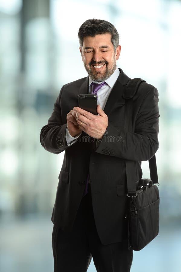 Mogen affärsman som använder mobiltelefonen fotografering för bildbyråer