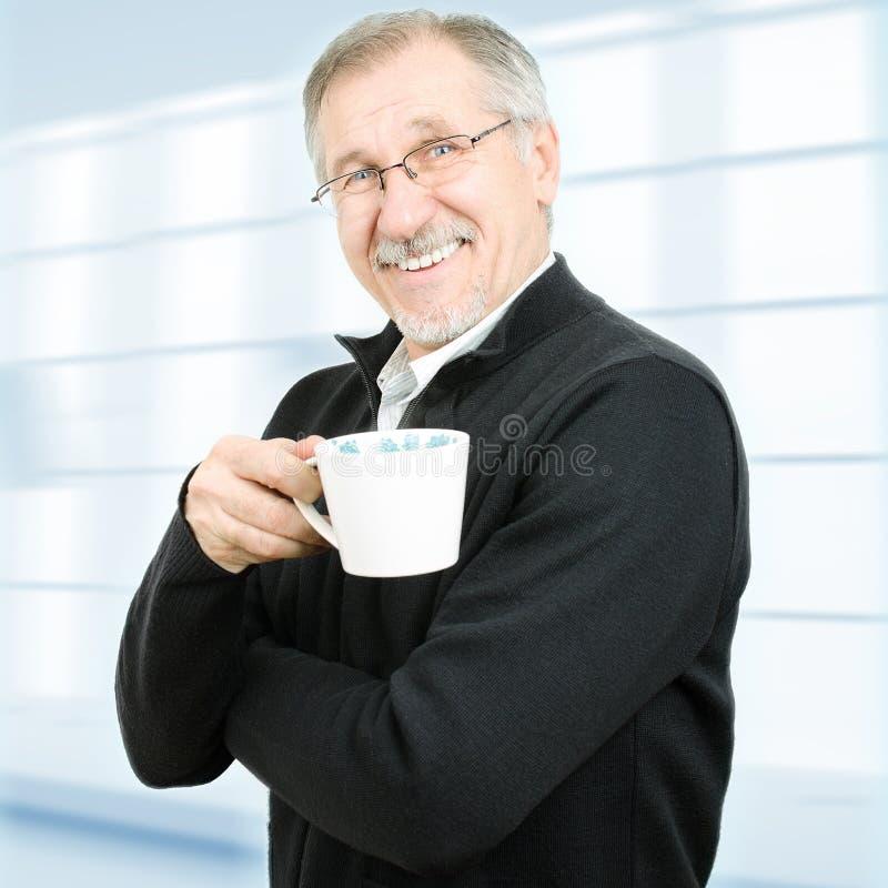 Mogen affärsman som har ett kaffeavbrott arkivbild