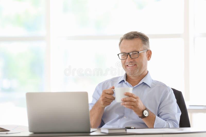 Mogen affärsman som i regeringsställning dricker kaffe på arbetsplatsen royaltyfri bild