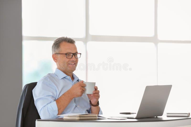 Mogen affärsman som i regeringsställning dricker kaffe på arbetsplatsen arkivbild