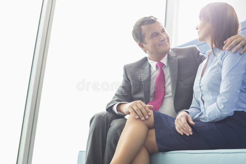 Mogen affärsman som i regeringsställning flörtar med den kvinnliga kollegan royaltyfria bilder