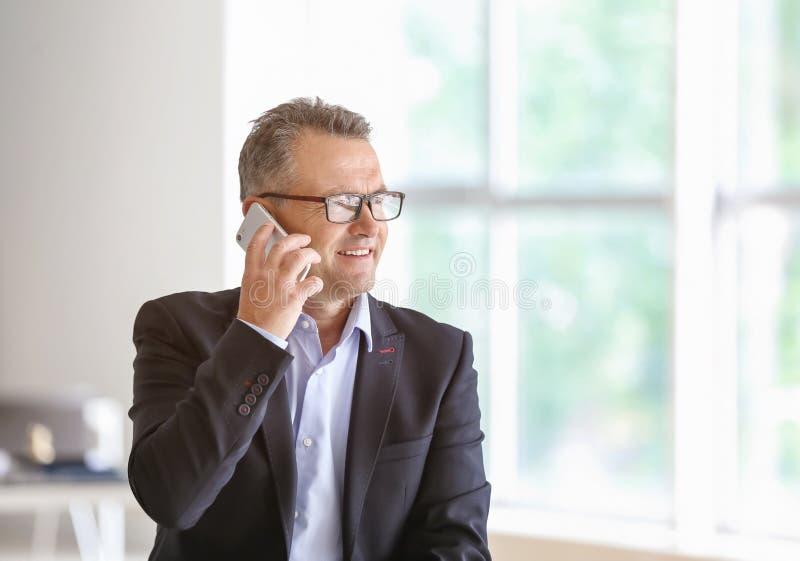 Mogen affärsman som i regeringsställning talar vid mobiltelefonen royaltyfri foto