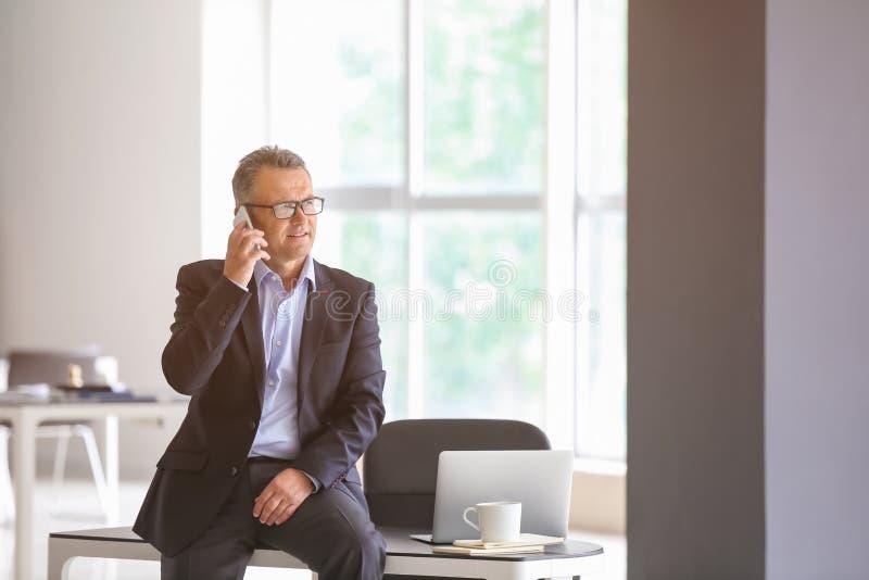 Mogen affärsman som i regeringsställning talar vid mobiltelefonen arkivfoton