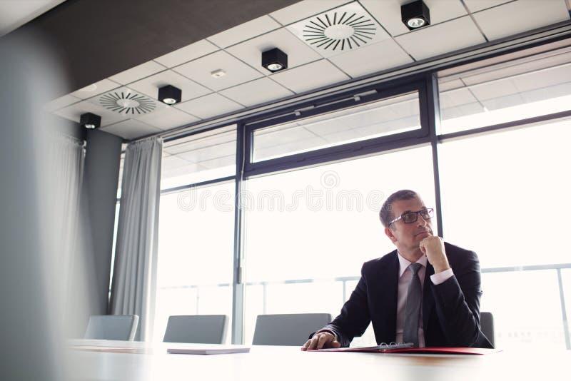 Mogen affärsman som lyssnar till möte i bräderum royaltyfri foto