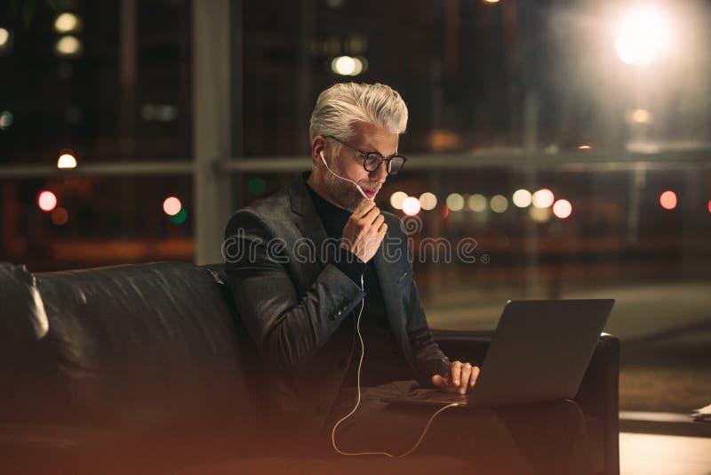 Mogen affärsman som sent i regeringsställning arbetar på natten royaltyfria foton