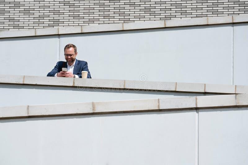 Mogen affärsman Using Mobile Phone som står utanför kontorsbyggnad arkivbild