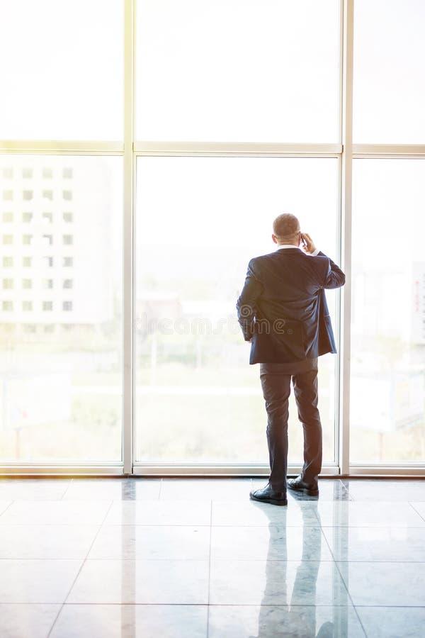 Mogen affärsresande för bakre sikt som talar på mobiltelefonen i flygplatsfolkhop med suddiga handelsresande i bakgrund arkivbild