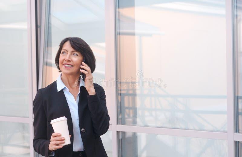Mogen aff?rskvinna som har ett avbrott framme av en kontorsbyggnad, talar p? telefonen och dricker kaffe royaltyfri foto