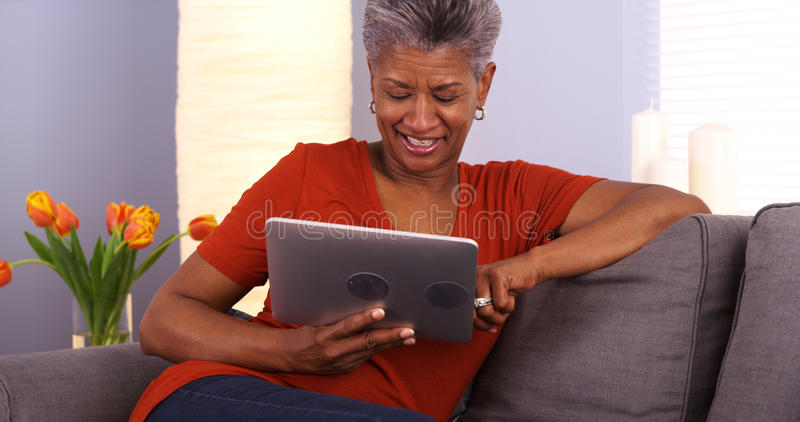 Mogen afrikansk kvinna som använder minnestavlan royaltyfria foton
