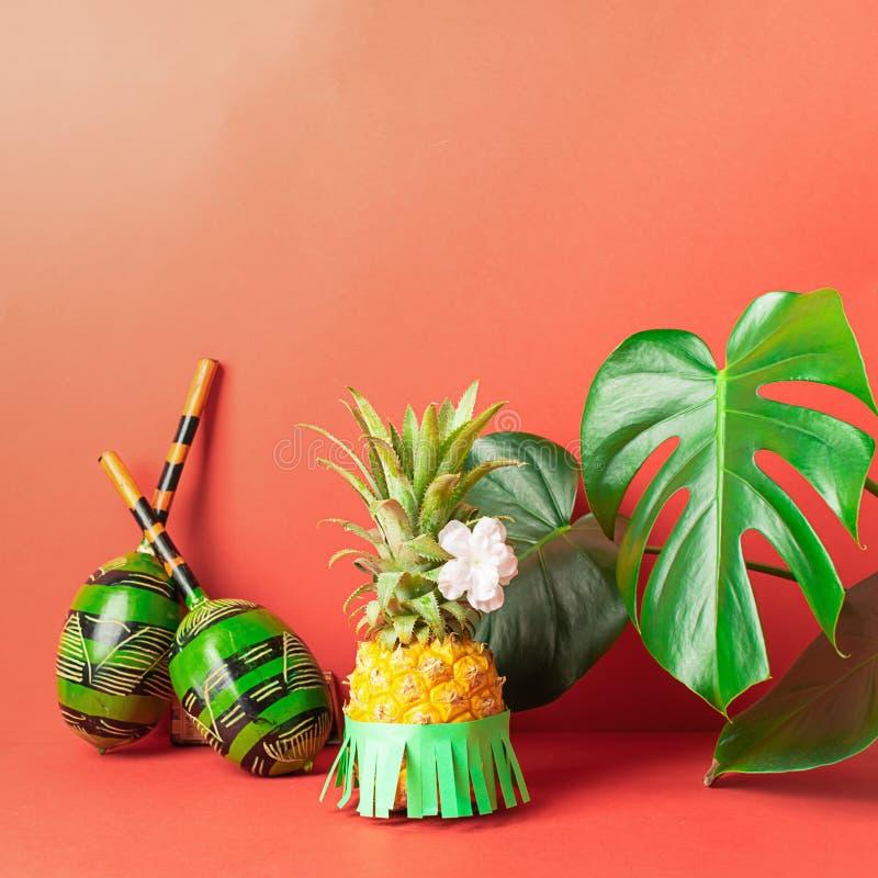 Mogen ananas i gröna maracas för en kjol på en röd bakgrund Rekreation- och partibegrepp Horisontal inrama royaltyfri foto