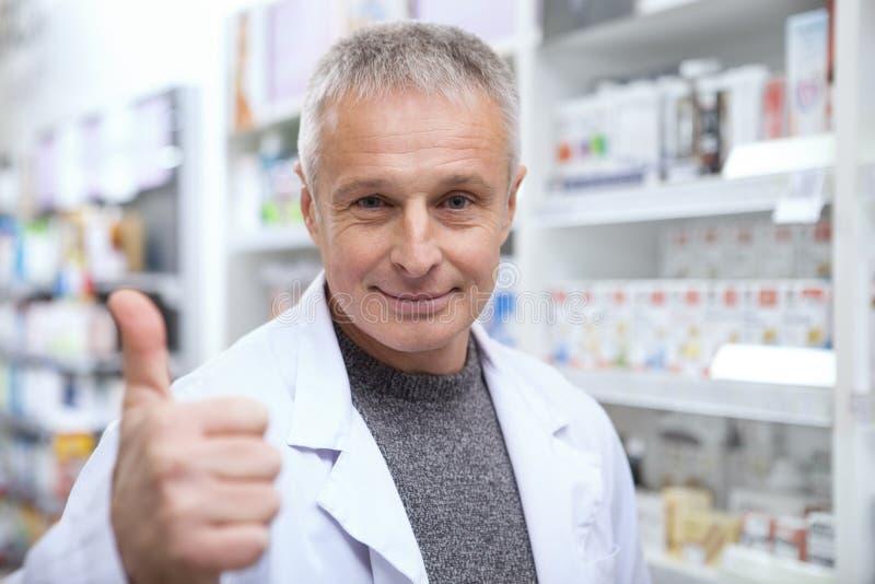 Mogen apotekare som hjälper hans kvinnliga kund royaltyfri bild
