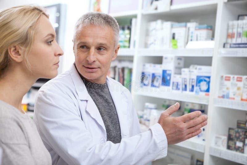 Mogen apotekare som hjälper hans kvinnliga kund arkivfoto