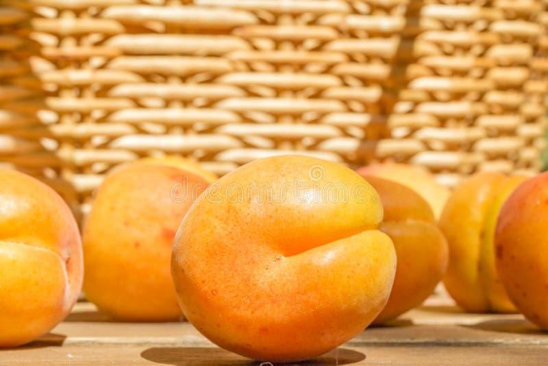 Mogen aprikosnärbild på suddig bakgrund av en vide- korg fotografering för bildbyråer