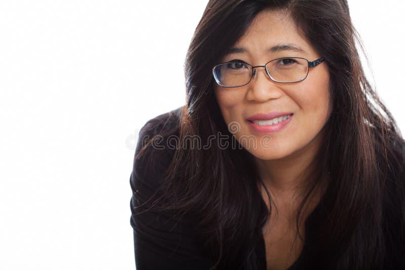 Mogen asiatisk kvinna i mitt- forties som bär exponeringsglas som ler arkivfoton
