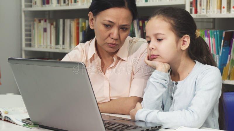 Mogen asiatisk kvinna som hjälper hennes trötta dotter med läxa arkivbild