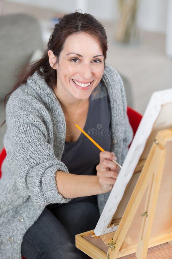 Mogen bautiful kvinnamålning på kanfas hemma arkivbild